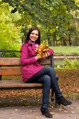 Jeune femme avec des feuilles de l'automne assis sur un banc — Photo