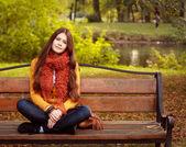 Chica en banco en el parque otoño — Foto de Stock