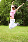 Sporty woman jumping on green grass — Stock Photo