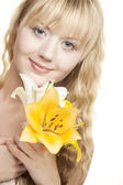 Beautiful blond girl with yellow lily — Stock Photo