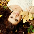 Woman lying on autumn leaves, outdoor portrait — Stock Photo