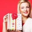 Happy blond woman with a gift — Stock Photo