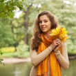 Young woman with autumn leaves in park — Stock Photo