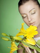Woman with yellow flowers on green background — Stockfoto