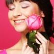 Happy woman holding pink rose — Stock Photo