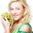Beautiful  blond woman holding a bunch of grape — Stock Photo