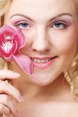 Beautiful woman with pink flower — Zdjęcie stockowe