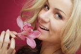 Beautiful happy woman with orchid flower — Stock Photo