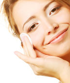 Young woman wipes a face skin — Stockfoto