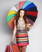 Woman with shopping bags and umbrella — Stock Photo