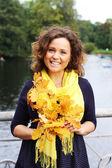 Mujer joven con hojas de otoño en el parque — Foto de Stock