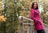 Fashion woman on bridge in autumn park — Stock Photo