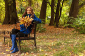 Elegant woman with autumn leaves sitting on bench — Stock Photo
