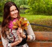 秋天的叶子坐在长凳上的女人 — 图库照片