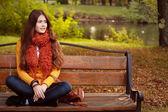 Kız sonbahar parktaki bankta — Stok fotoğraf