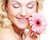 Mulher jovem e bonita com flor de gerber — Fotografia Stock