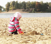 Little girl playing with sand at the autumn beach — Stock Photo