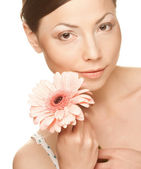 Young woman with gerber flower — Stock Photo