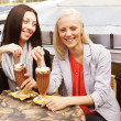 Smiling women drinking a coffee sitting — Stock Photo #39177965