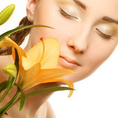Beauty woman face with yellow lily flower — Stok fotoğraf