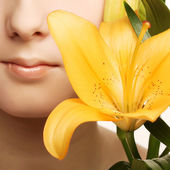 Beauty woman face with yellow lily flower — Stock Photo