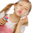 Funny lovely little girl blowing soap bubbles — Stock Photo #39214557