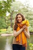 公园里的秋叶的年轻女人 — 图库照片