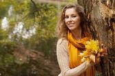 青年微笑着女人在秋天公园 — 图库照片