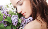 Frühling mädchen mit lila blumen. — Stockfoto