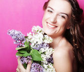 Girl with lilac flowers over pink background — Stockfoto