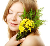 Woman with small yellow flowers — Stock Photo