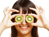 Woman holding kiwi fruit for her eyes. — Stock Photo