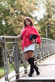 Fashion woman on bridge in autumn park — Stock Photo
