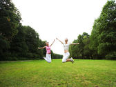Two young girls jump in summer park. — Stock Photo