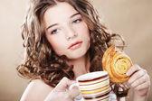 Kvinna äter cookie och dricker kaffe. — Stockfoto