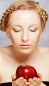 Smiling woman eating red apple — Stock Photo