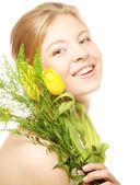 Junge, lächelnde frau mit gelben tulpen — Stockfoto
