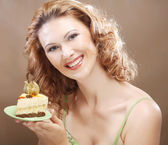 Young woman holding up a delicious piece of cake — Stock Photo