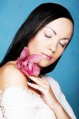 Joven bella mujer con flor rosa — Foto de Stock