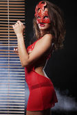Attractive woman in red with mask — Stockfoto