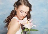 Beautiful woman with a lily flowers — Stock Photo