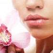 Young woman with pink orchid — Stock Photo