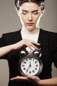 De zakenvrouw met een wekker — Stockfoto