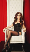 Sensual woman in lingerie sitting on throne — Stock Photo