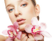 Beautiful woman with a orchid  flowers. — Stock Photo