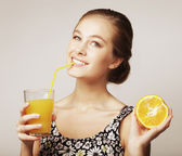 Woman holding orange and orange juice — Stock Photo