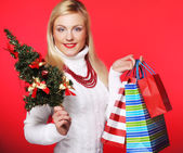 Woman holding gift  and the tree — Stock Photo