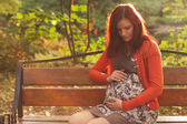 Pregnant woman walking in autumn park — Stock Photo