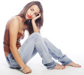 Girl with tattered jeans sit on floor — Stock Photo