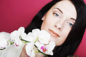 Beautiful healthy woman with orchid flower. — Stock Photo